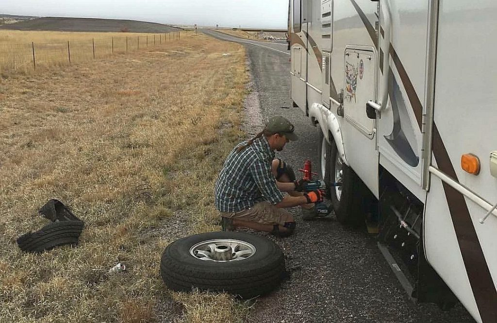 Changing a flat tire (both actually, due to the non-blow out damaging the remaining tire); photo credit: Jason Simpson