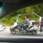 Guy on scooter loaded with bags and gear