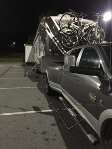 Truck and camper in a parking lot with extension cord running to the camper