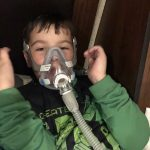 Child wearing father's CPAP mask