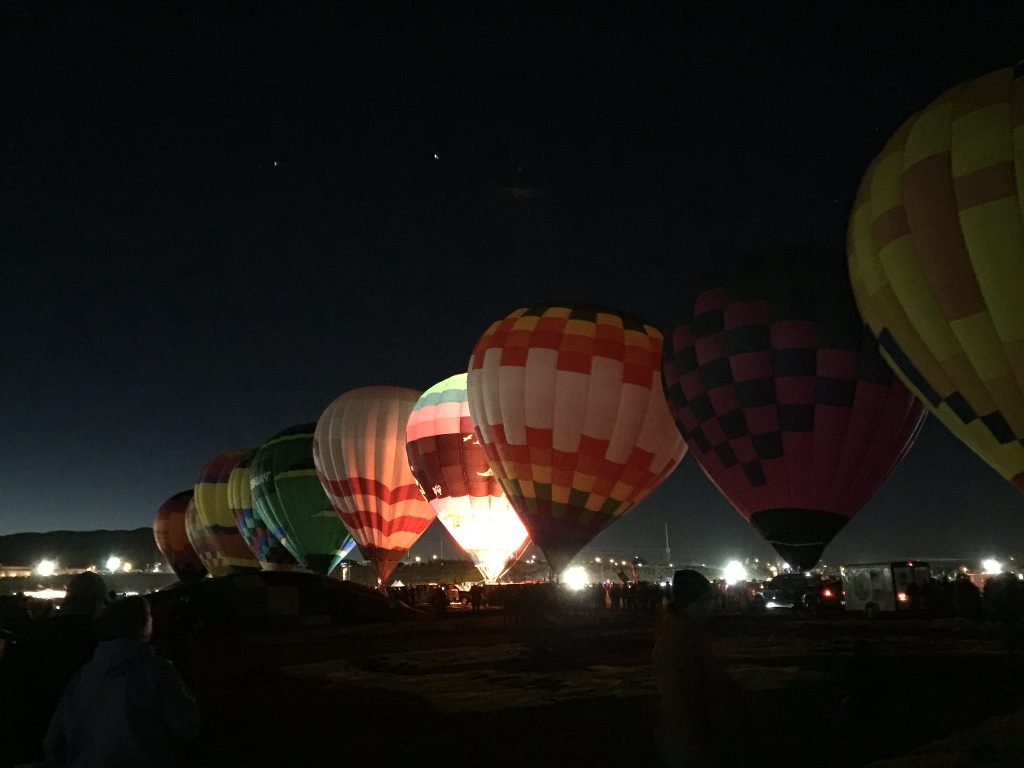 Pre-dawn picture showing hot air balloons in a line being inflated