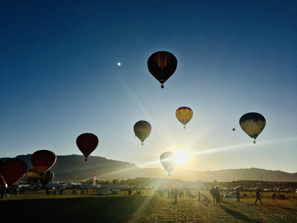 Hot air balloons in the early morning with the sun peaking out behind a balloon