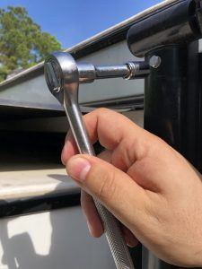 Socket wrench being used to remove a bolt at the end of an RV awning arm